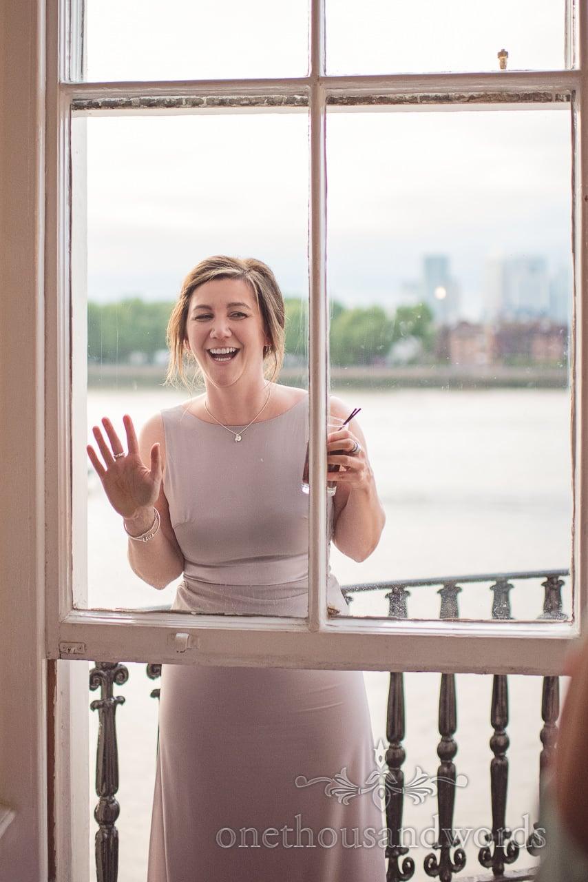 Bridesmaid looks in through window overlooking Thames on Trafalgar Tavern balcony