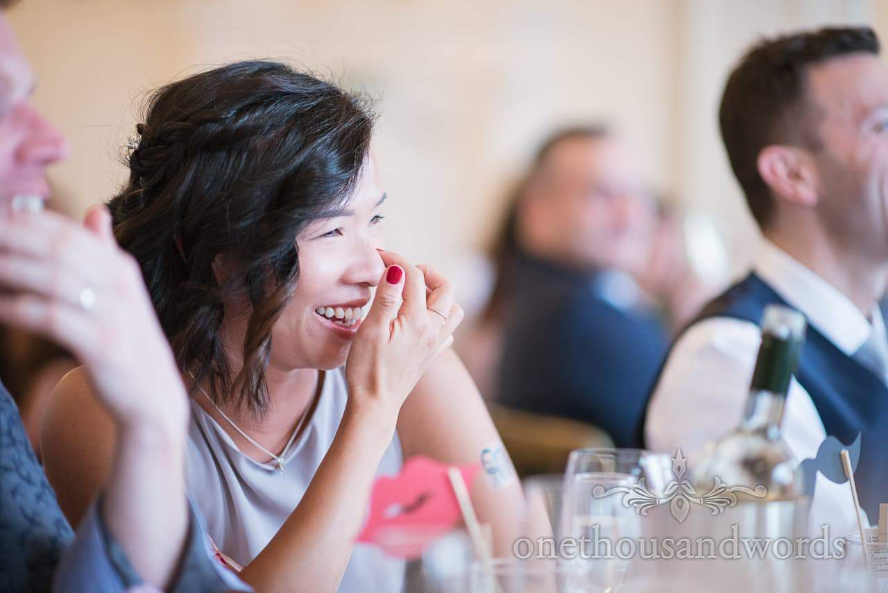 Bridesmaid portrait photograph laughing during wedding speeches