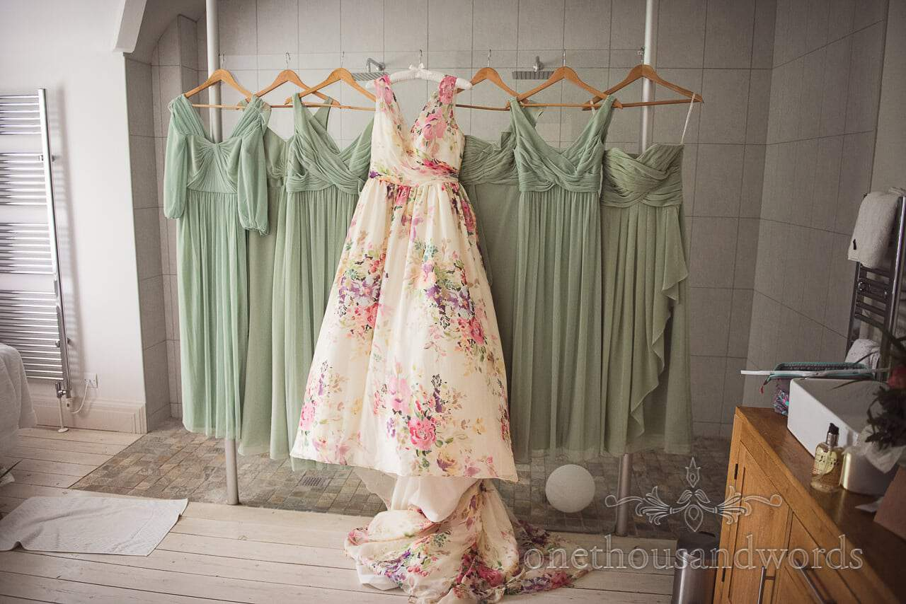 Bridesmaids and Brides dresses hang in the bathroom