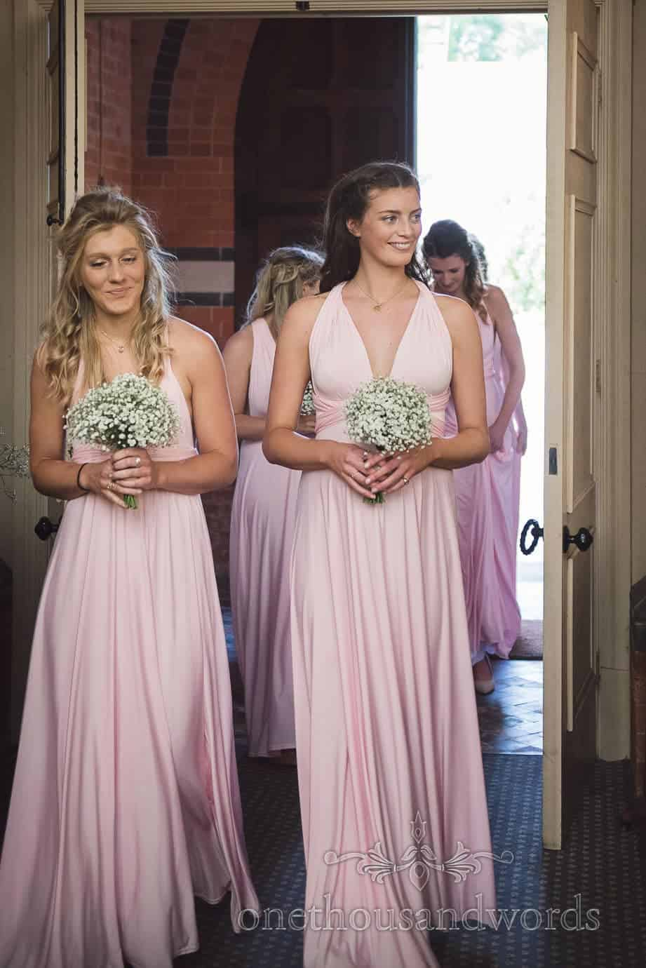 Bridesmaids in dusty pink Greco-Roman dresses enter church wedding ceremony