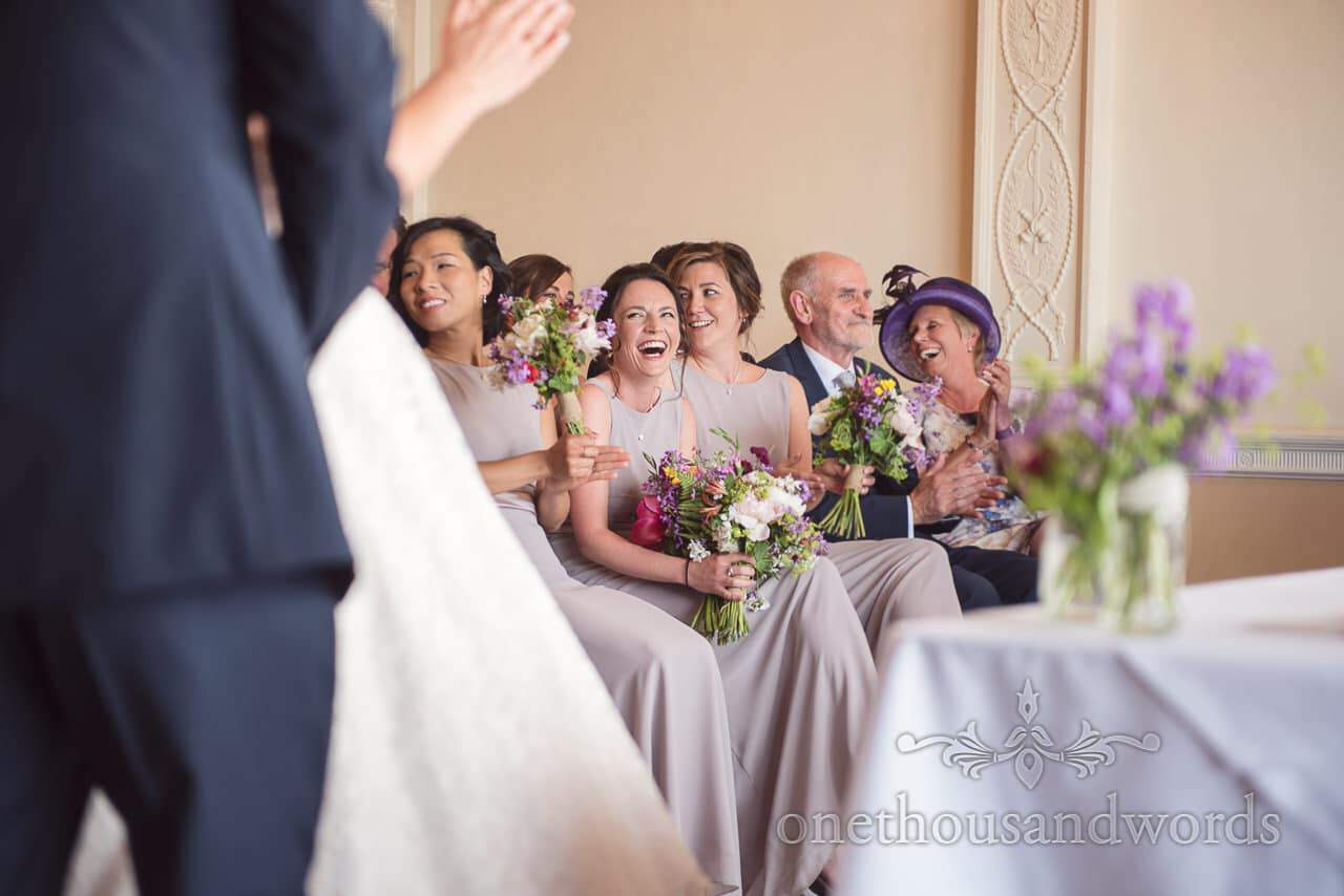 Bridesmaids in dusty violet bridesmaids dresses laughing during Greenwich wedding ceremony