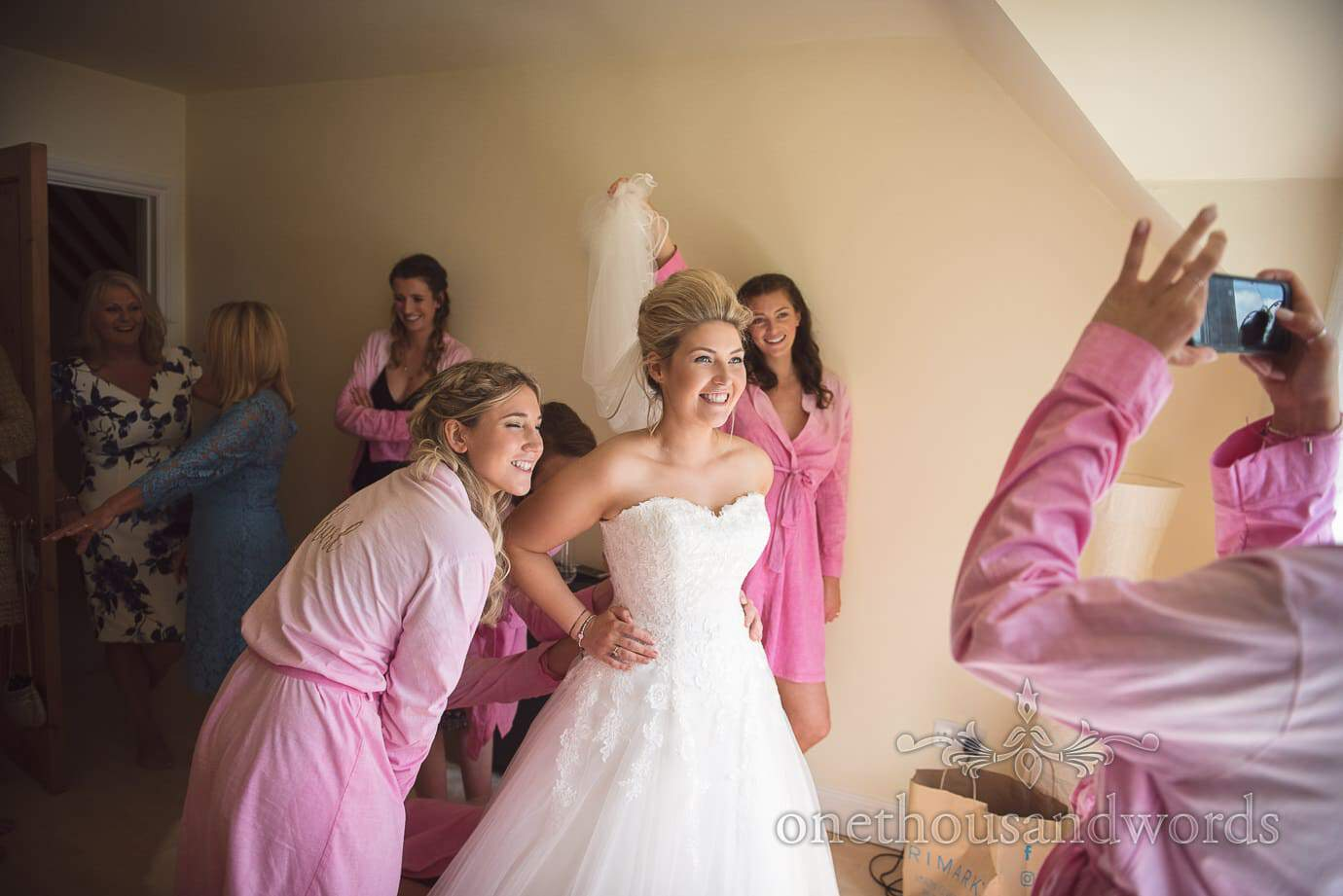 Bridesmaids in pink dressing gowns help bride into wedding dress and take photograph