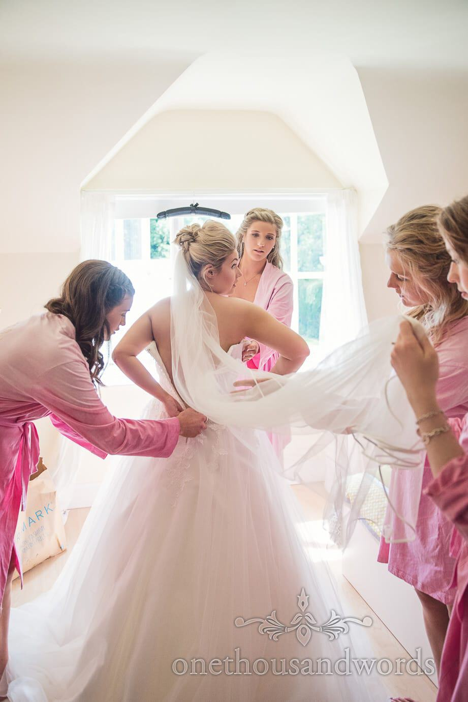 Bridesmaids in pink zip bride into white wedding dress with veil