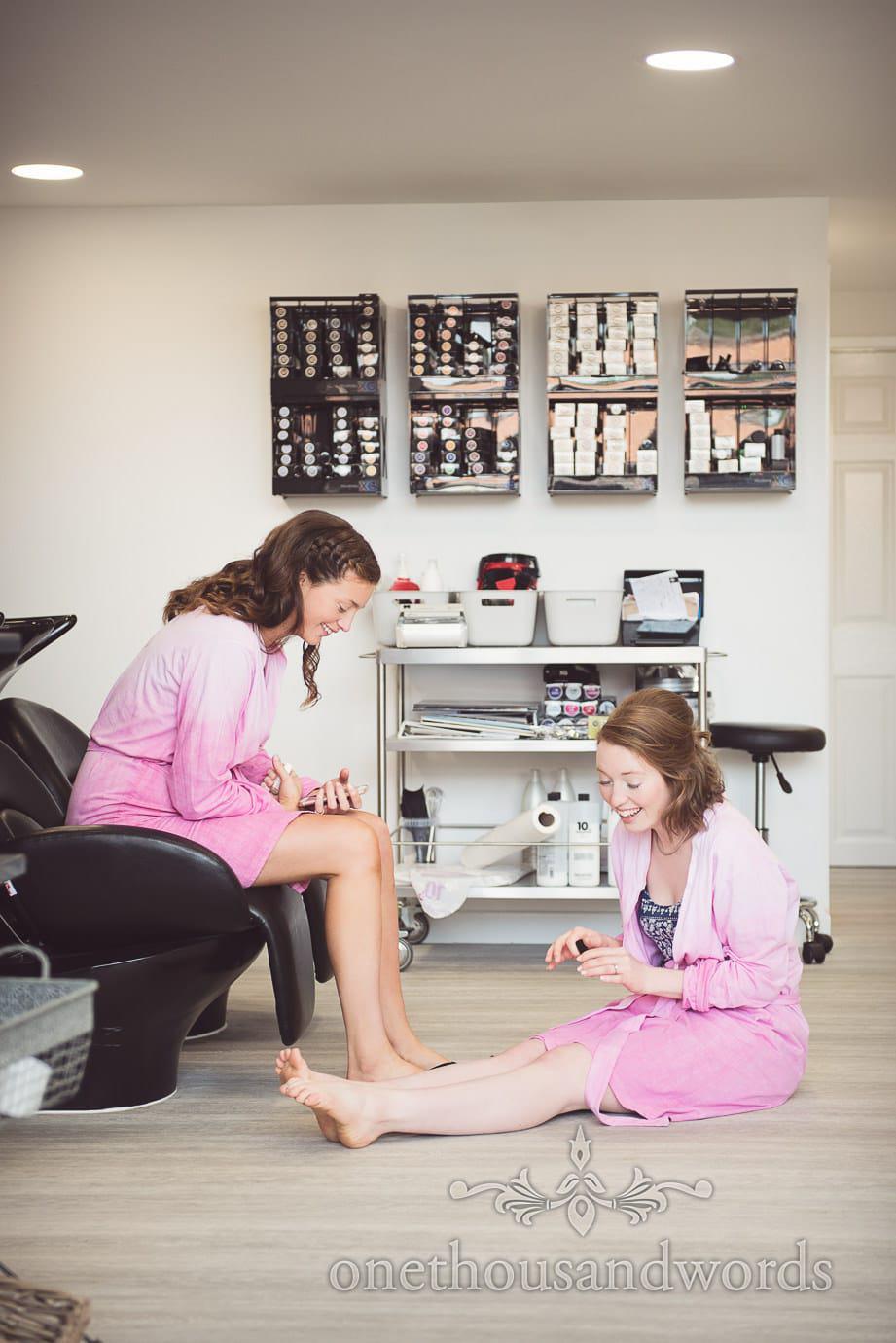 Bridesmaids paint their toenails at beauty salon during wedding morning preparations