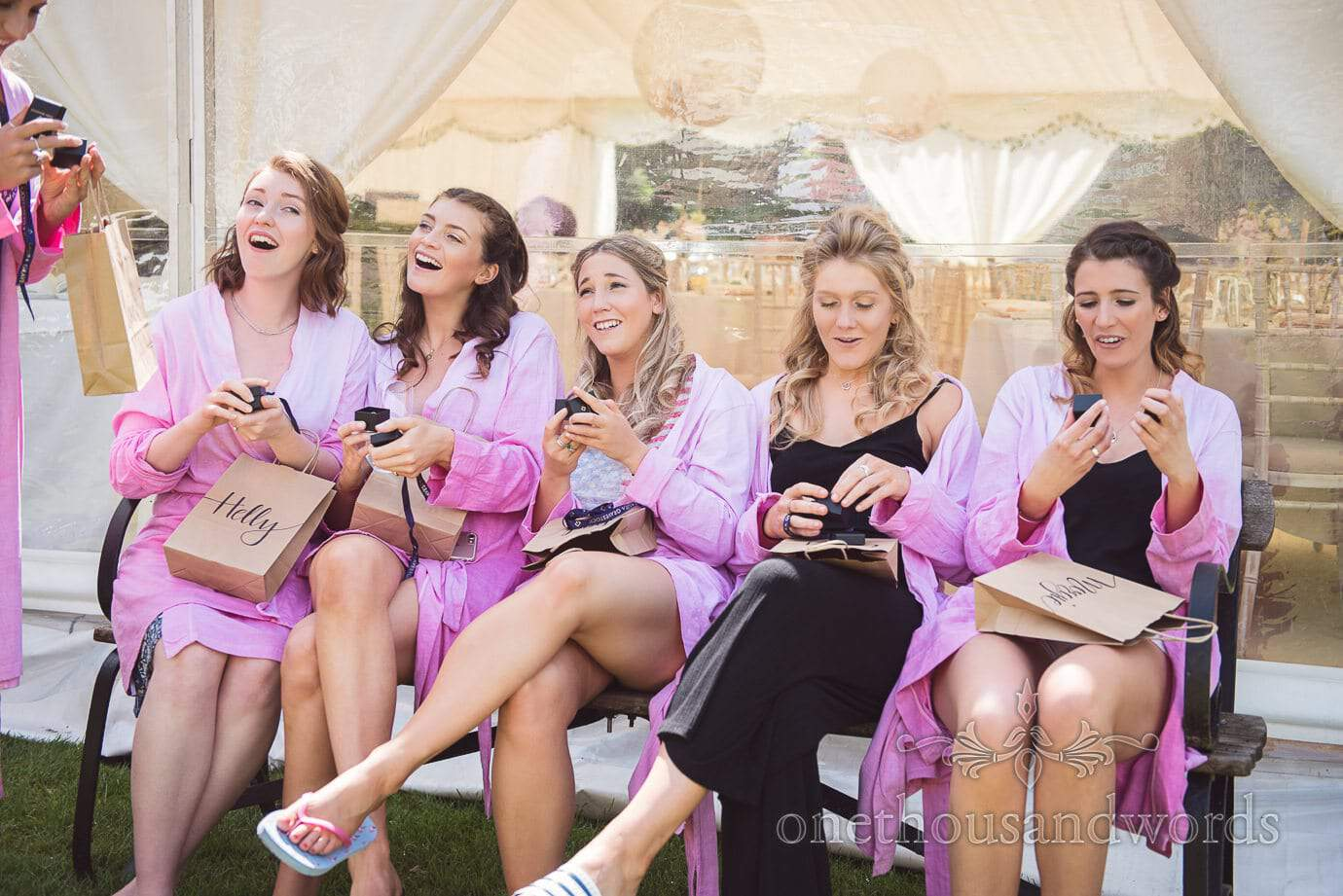 Bridesmaids receive gifts from bride in personalised paper bags on wedding morning