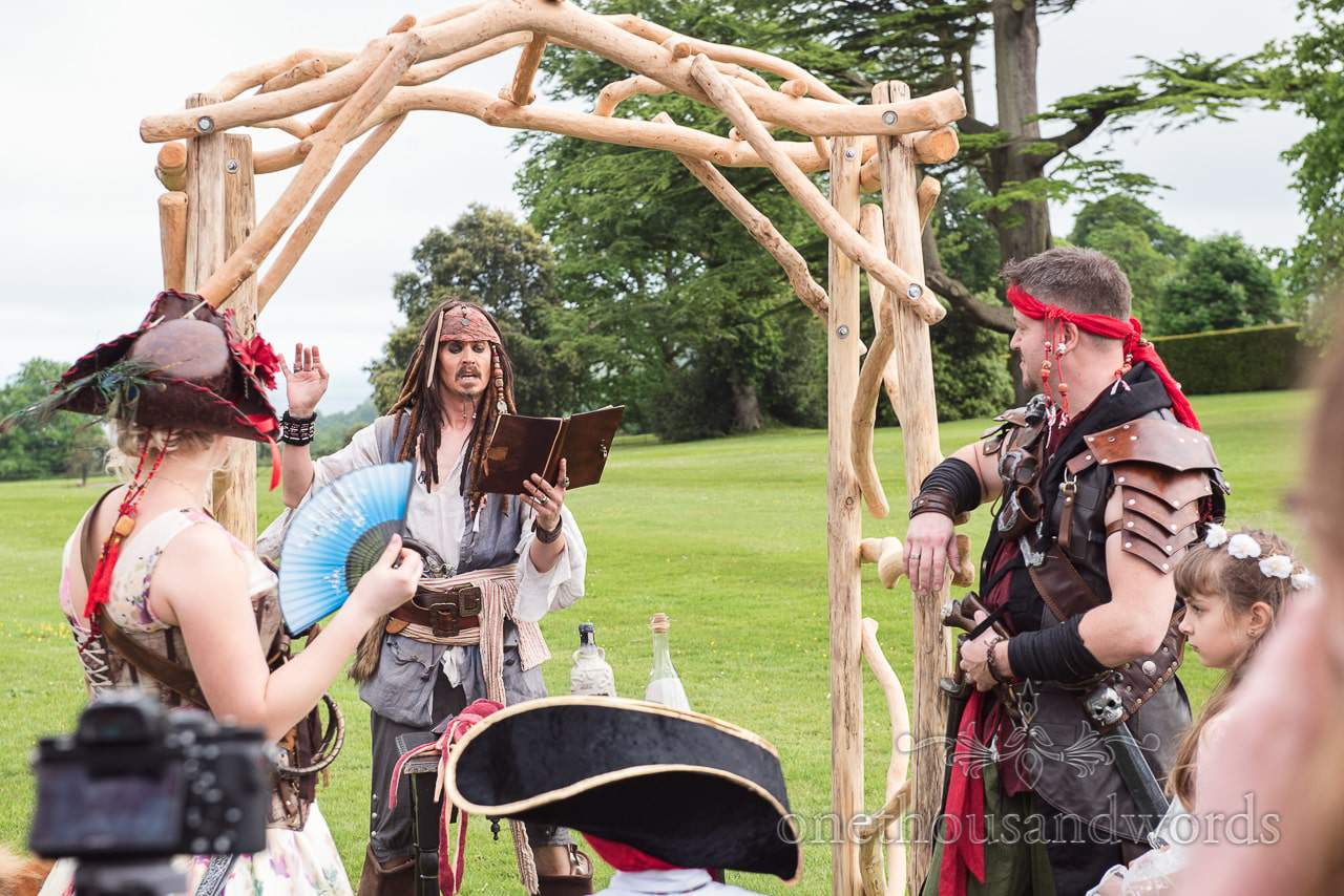 Captain Jack Sparrow holds pirate wedding ceremony under driftwood archway
