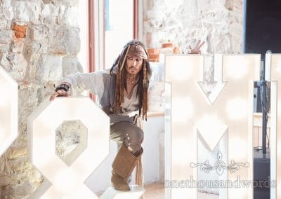 Captain Jack Sparrow lookalike Melo Sparrow with illuminated letters at pirate themed wedding