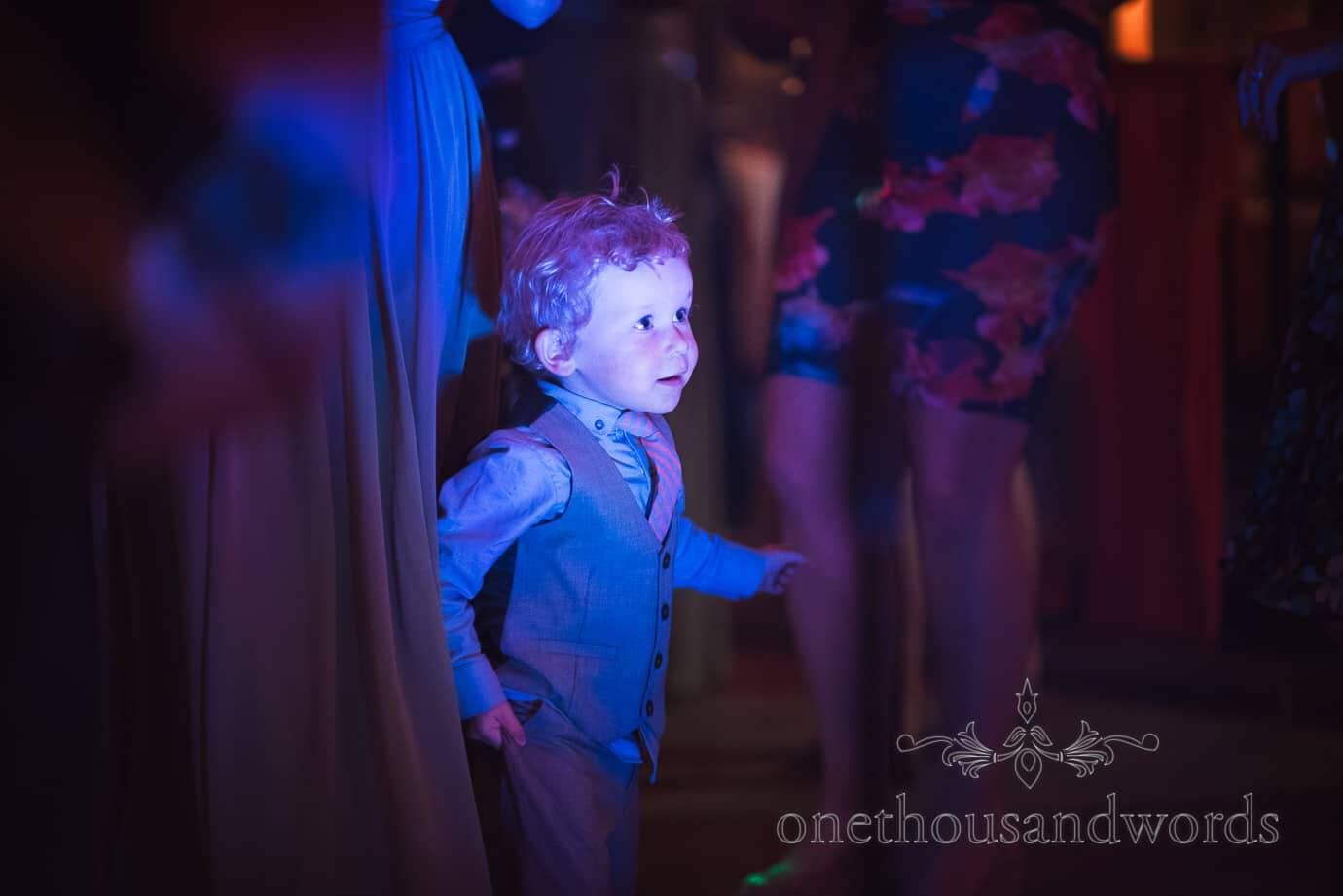 Child wedding guest dances under blue disco lights on the dance floor at Barn wedding
