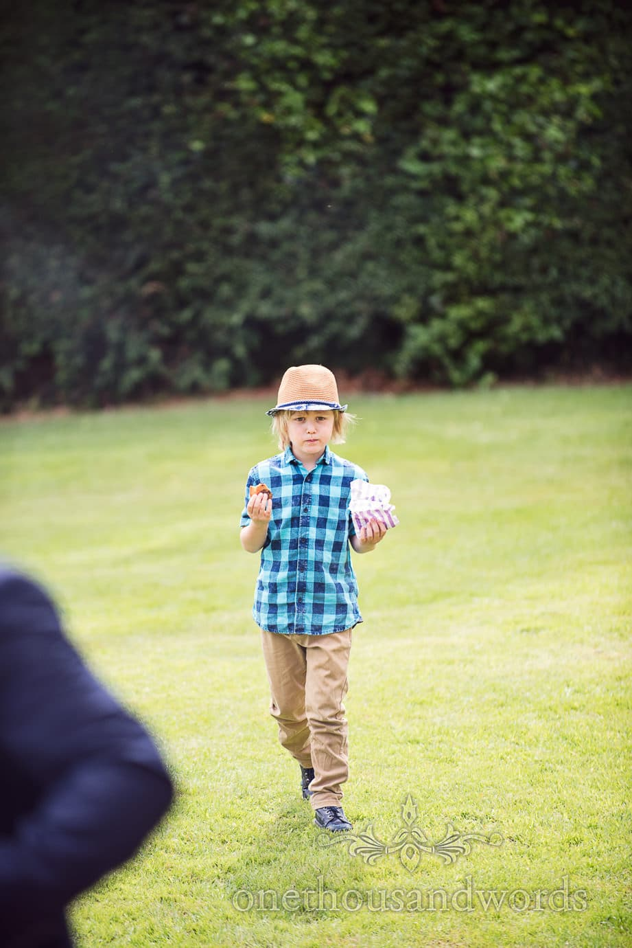 Child wedding guest in blue checked shirt and straw hat at country wedding