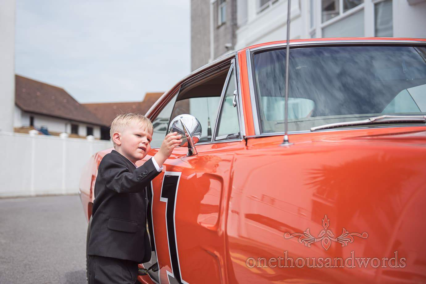 Child wedding guest inspects The General Lee wedding car at Rock and Roll wedding