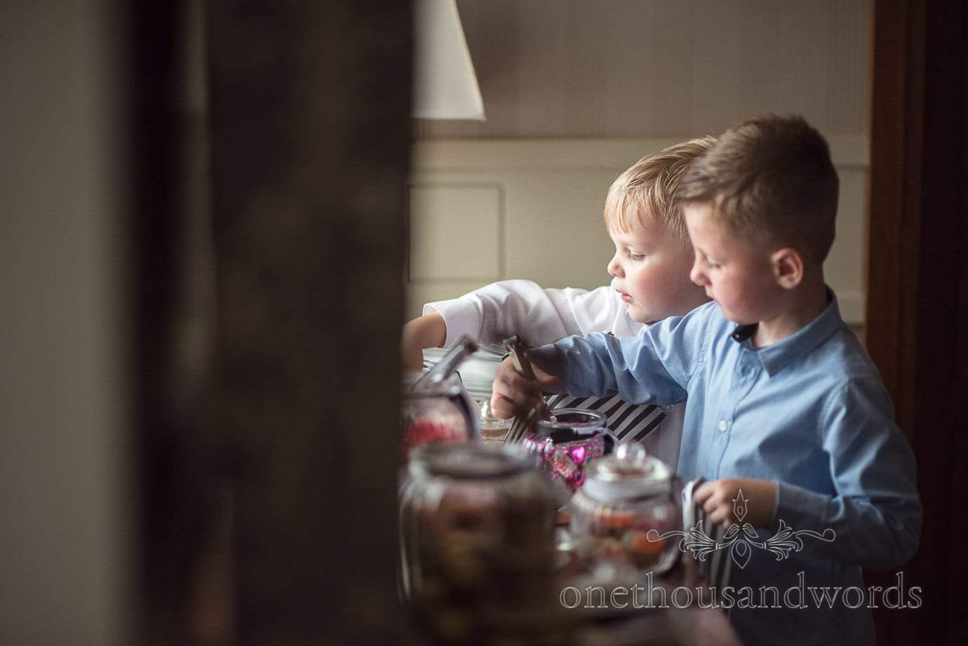 Child wedding guests help themselves to wedding pick and mix sweets in jars