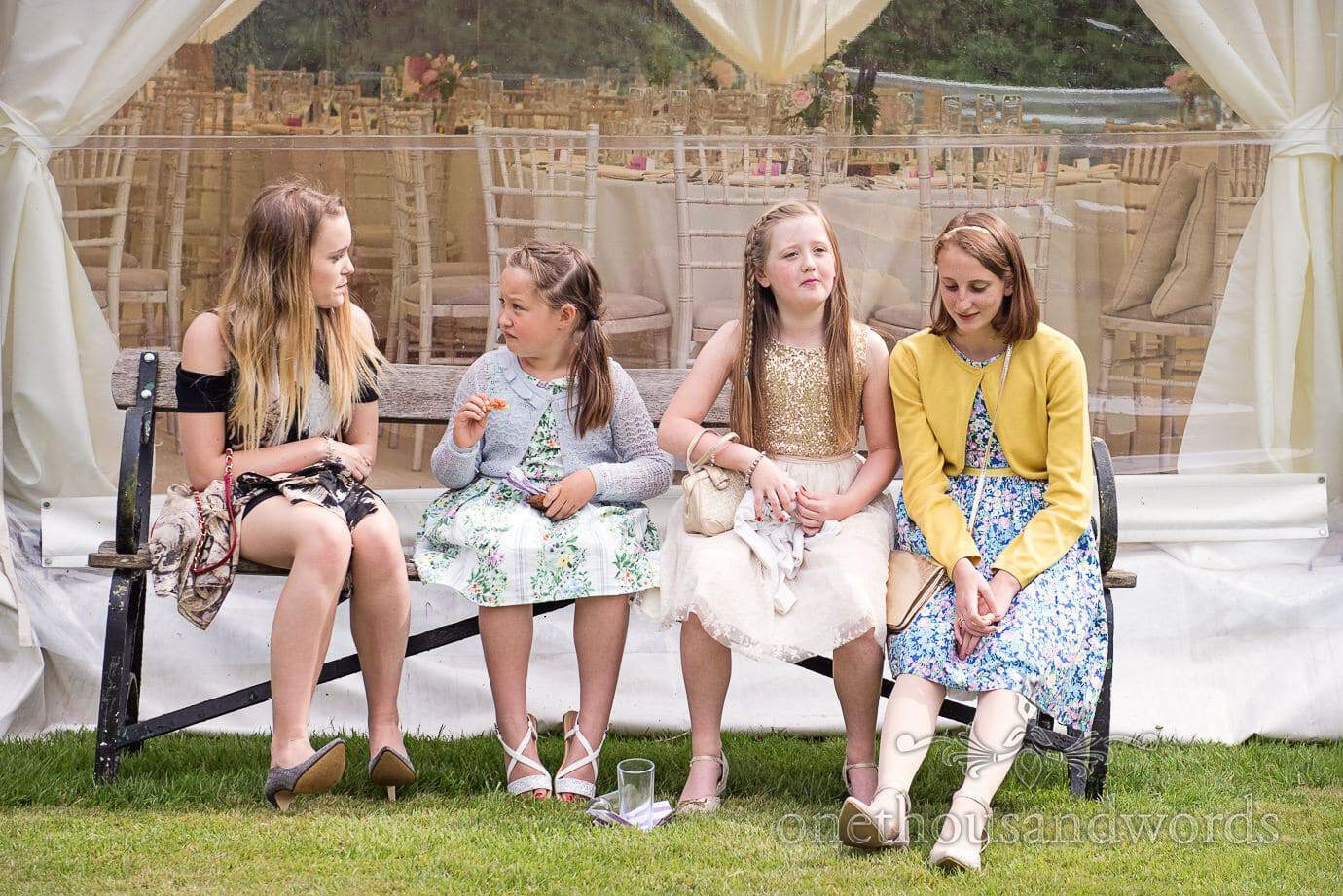 Child wedding guests on bench in shade at marquee wedding