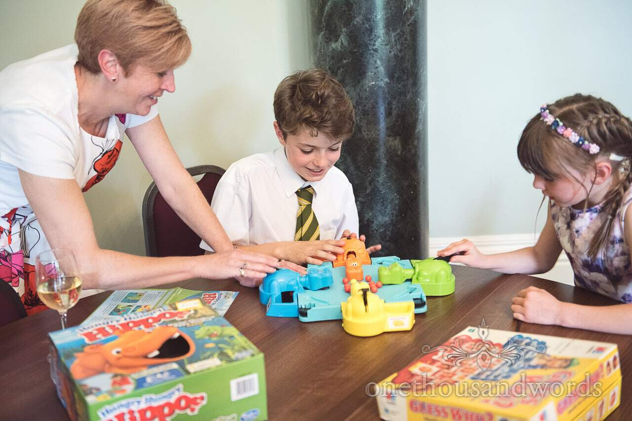 Child wedding guests play Hungry Hippos board game at Upton House wedding