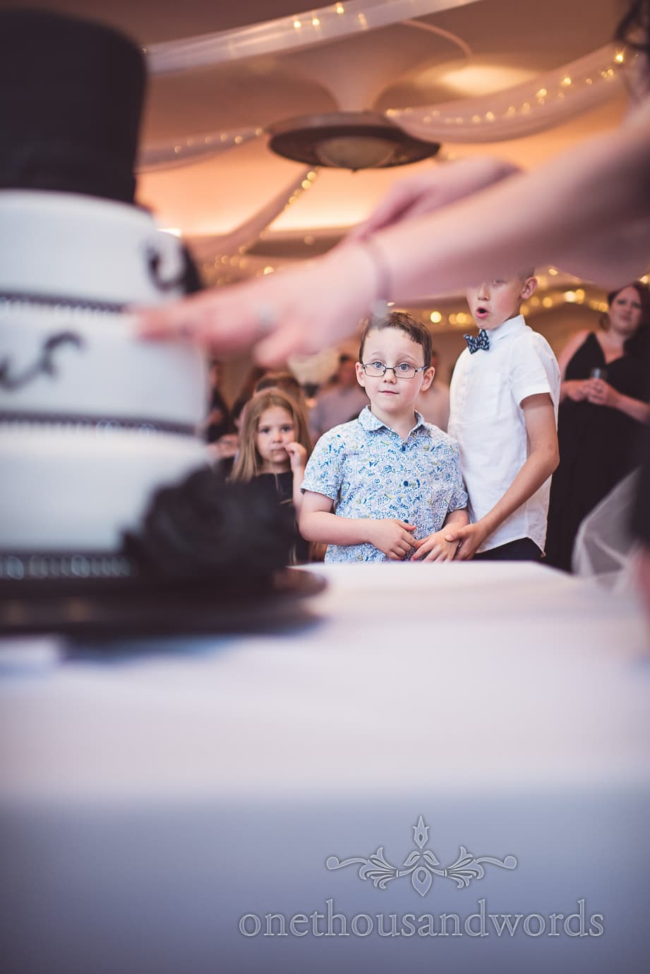 child wedding guests watch cutting of the cake with black and white wedding cake