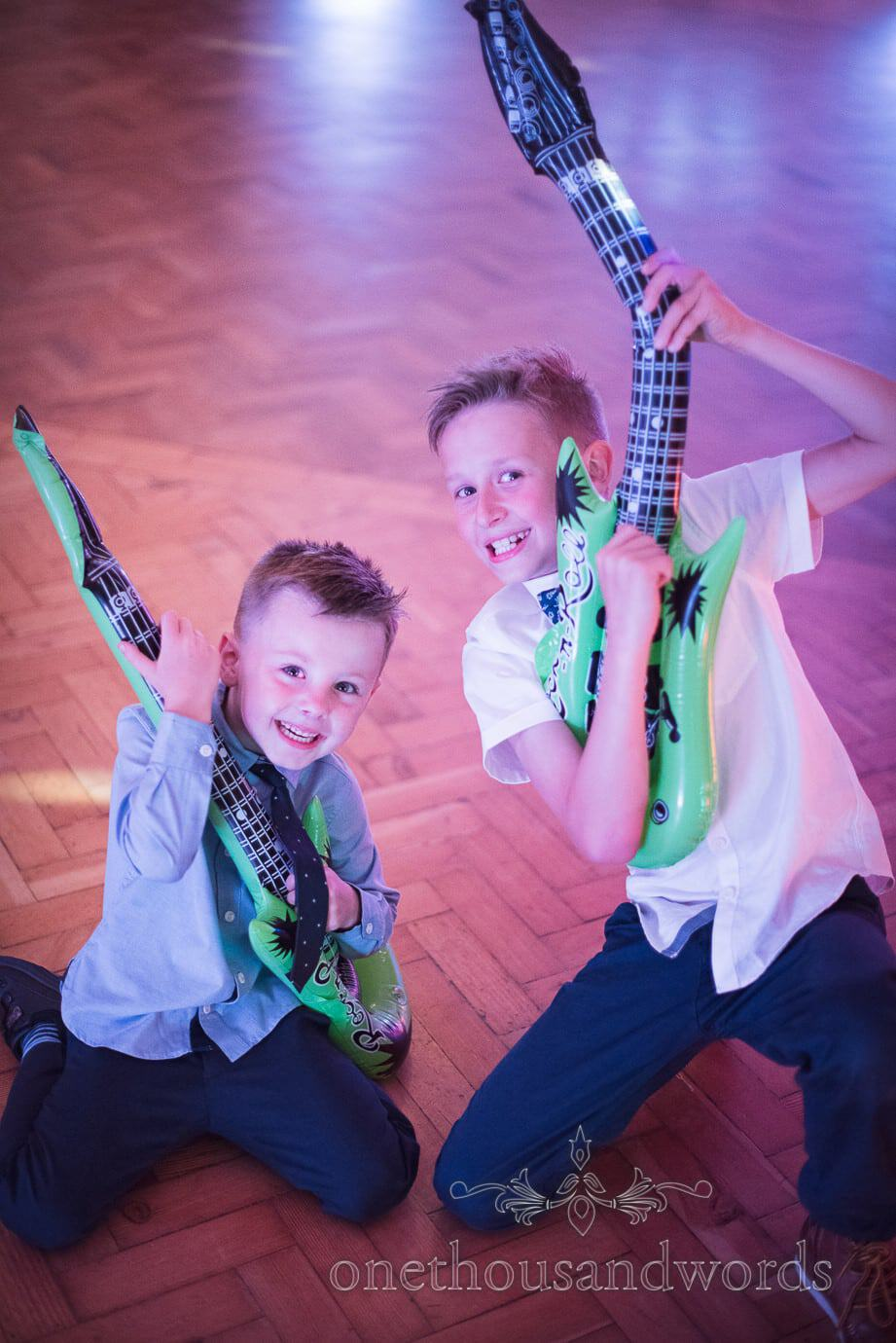 Children play inflatable guitars on dance floor at rock and roll themed wedding photographs
