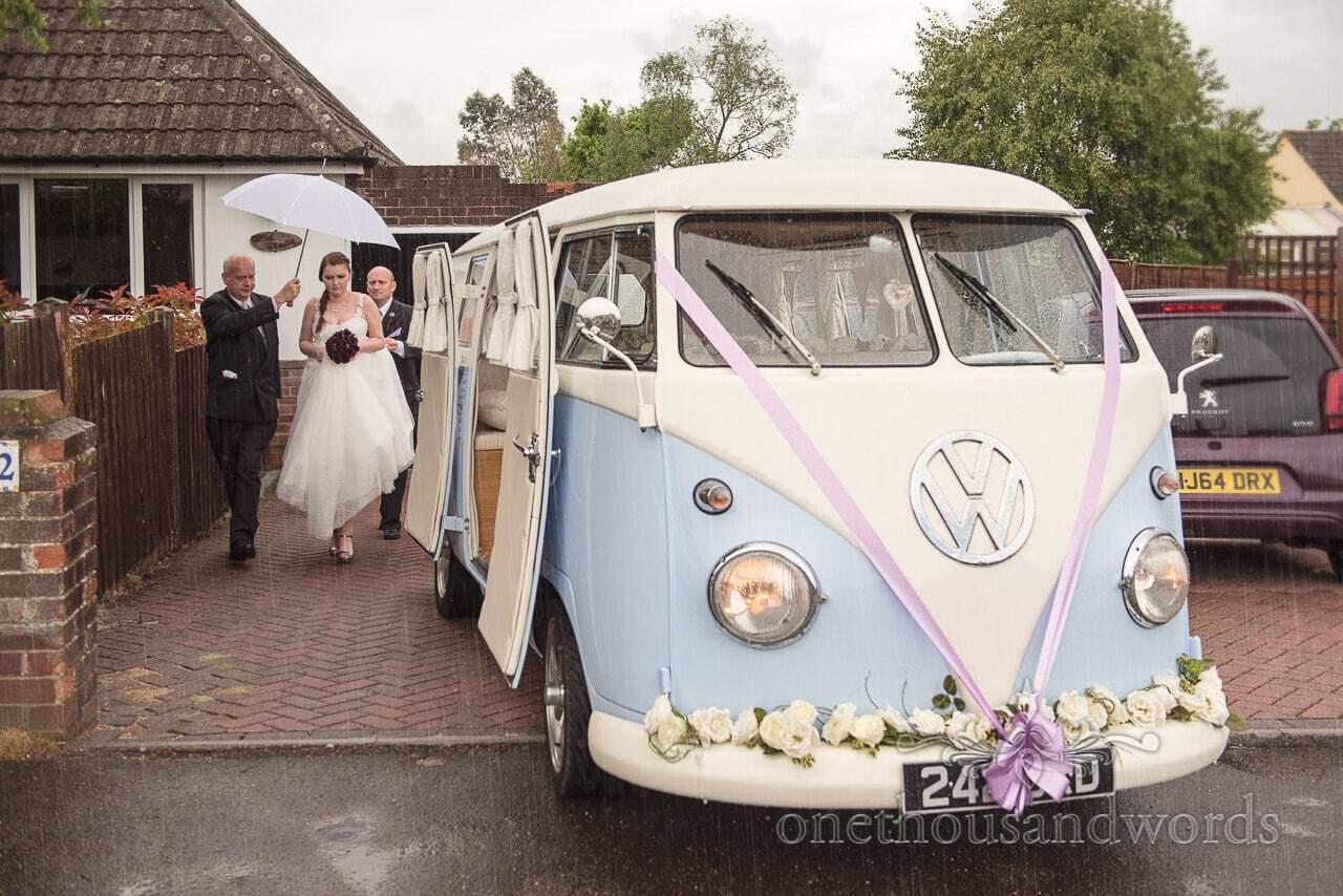 Classic split screen VW wedding van in the rain on wedding morning