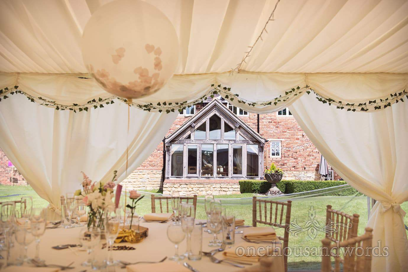 Country house seen from wedding marquee on the lawns at country wedding