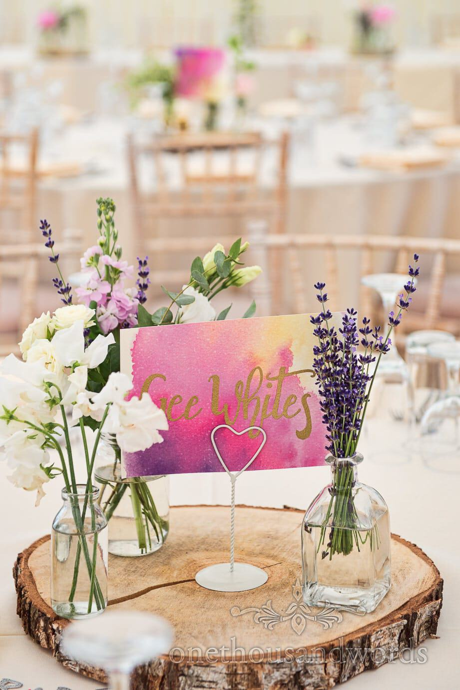 Country wedding name place sign with gold script on wooden tree slice in wedding marquee