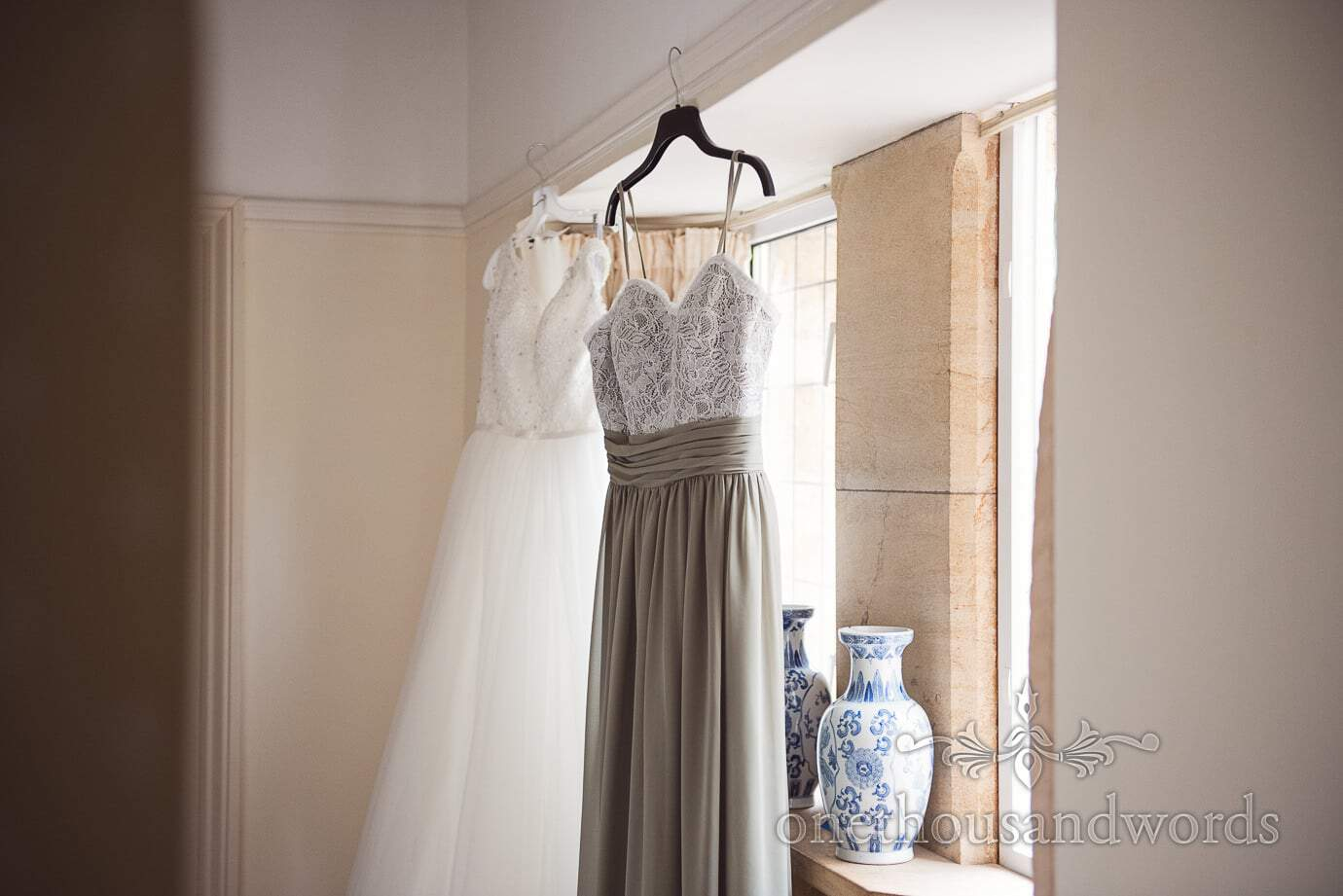 Dusty green bridesmaids dress hangs in window with white wedding dress