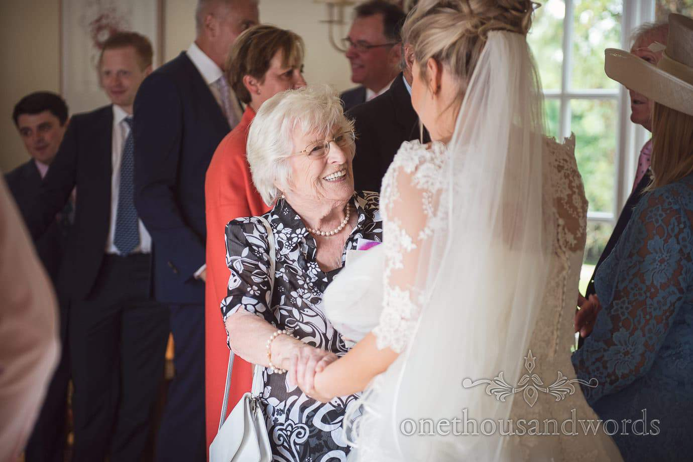 Elderly wedding guest in black and white floral dress with pearls greets bride
