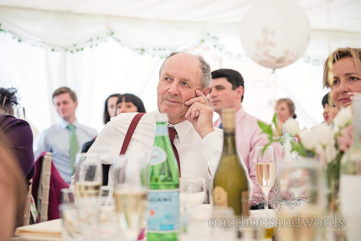 Elderly wedding guest in red braces and red tie listens to wedding speeches in marquee