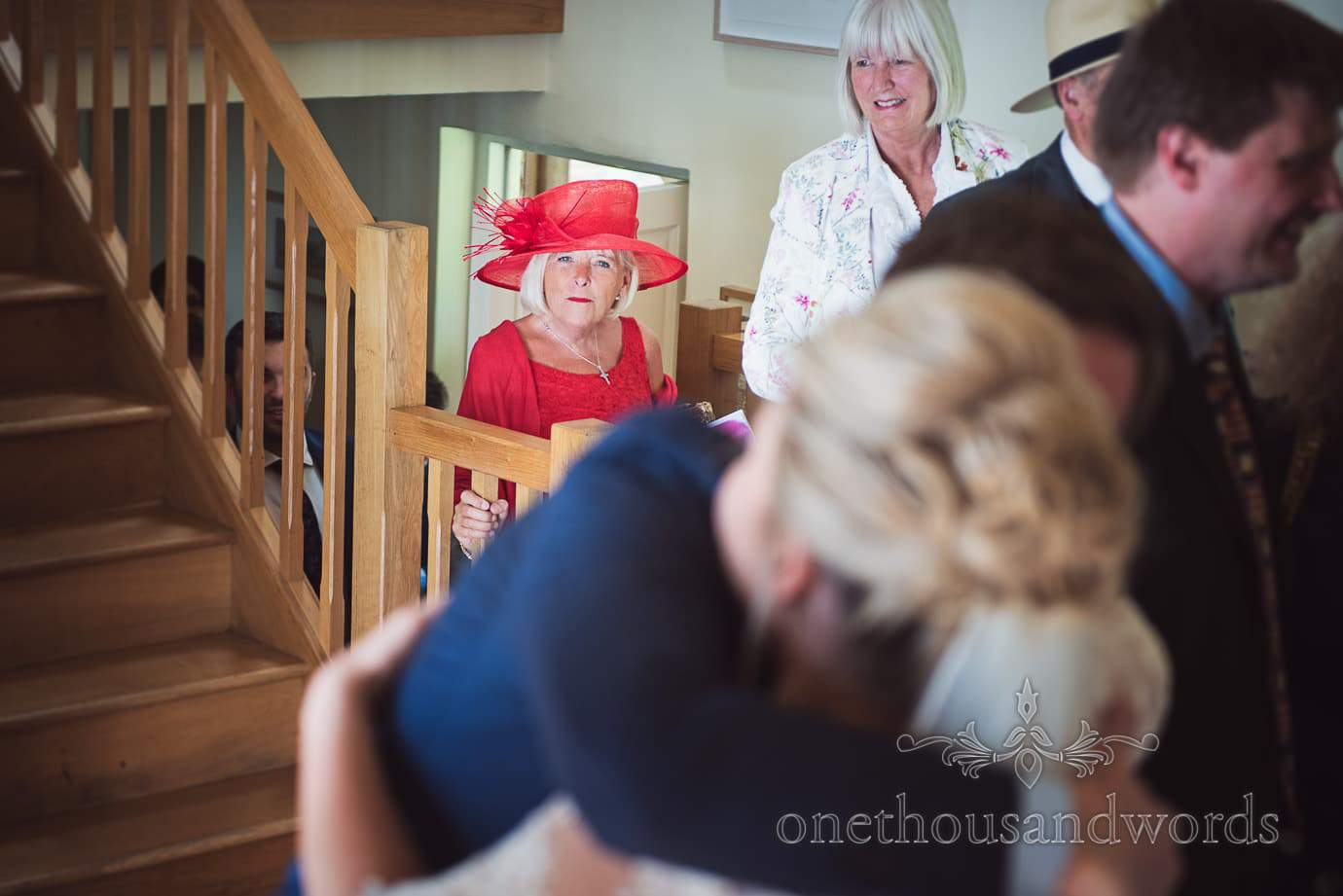 Elderly wedding guest in red wedding outfit climbs stairs to receiving line