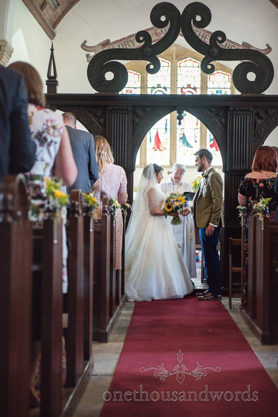 English church wedding ceremony under amazing dark wooden carved archway