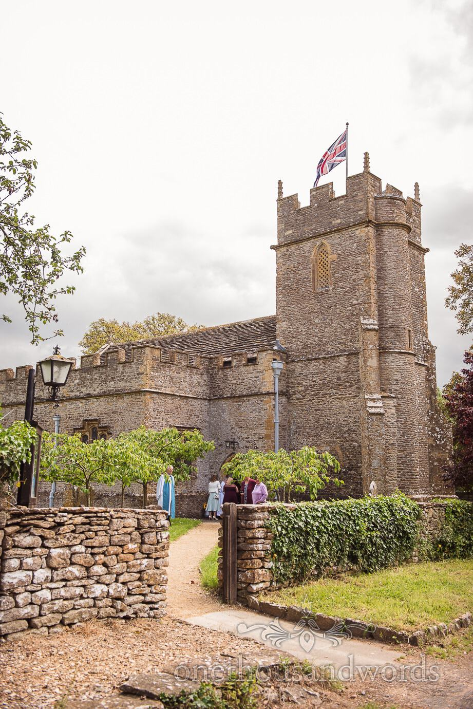 English countryside stone church flies union jack with vicar and guests on wedding morning
