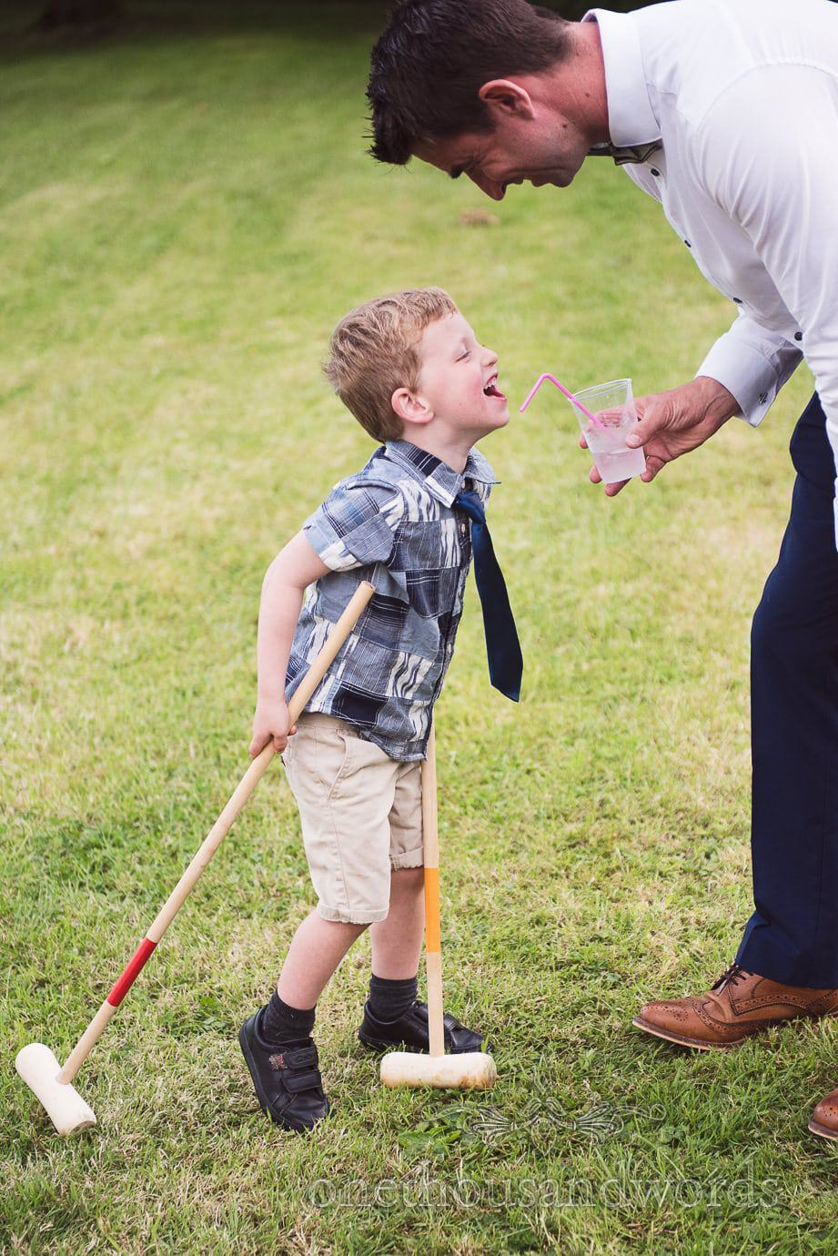 Father jokes around with son with croquet mallets at rustic barn wedding in the countryside