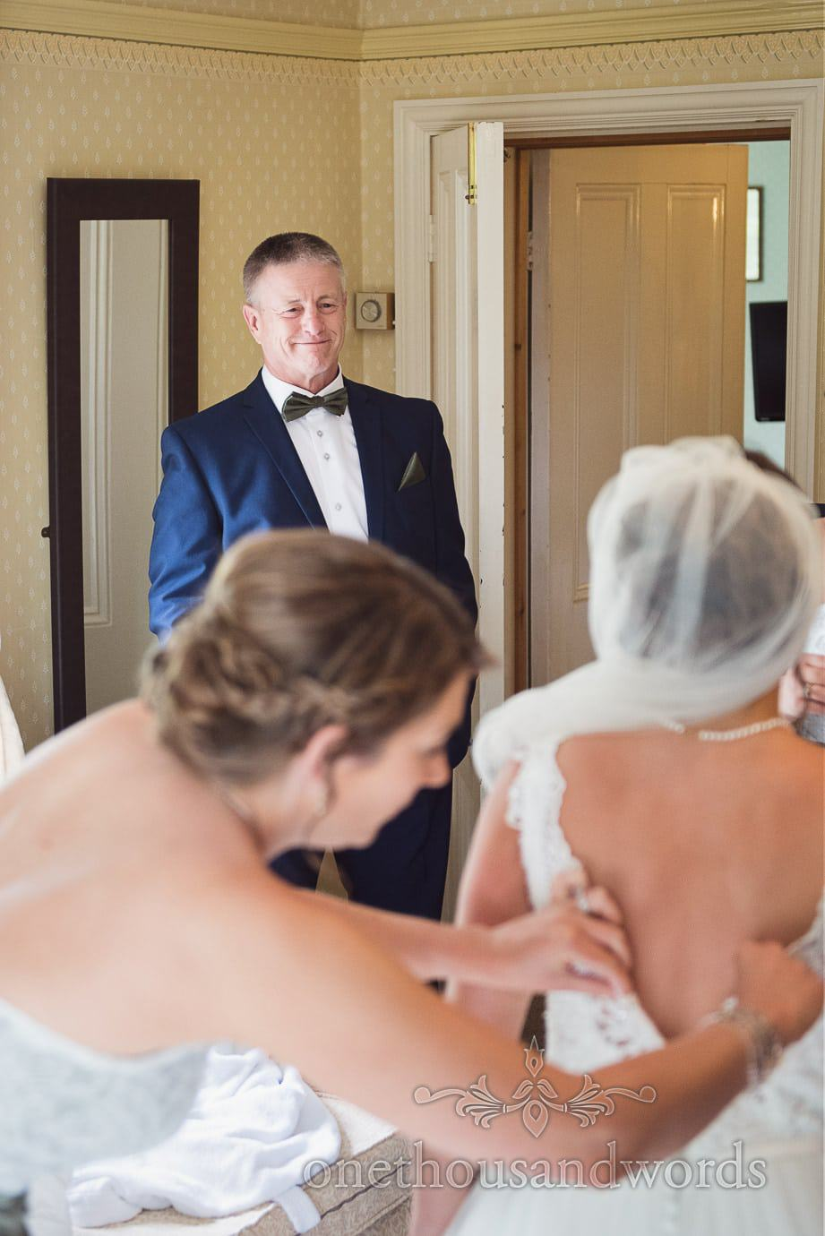 Father of bride in bow tie sees bride in wedding dress for the first time on wedding morning in Dorset