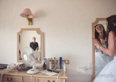 Father of bride watches bride preparation in Hotel room mirrors at Rock and Roll wedding