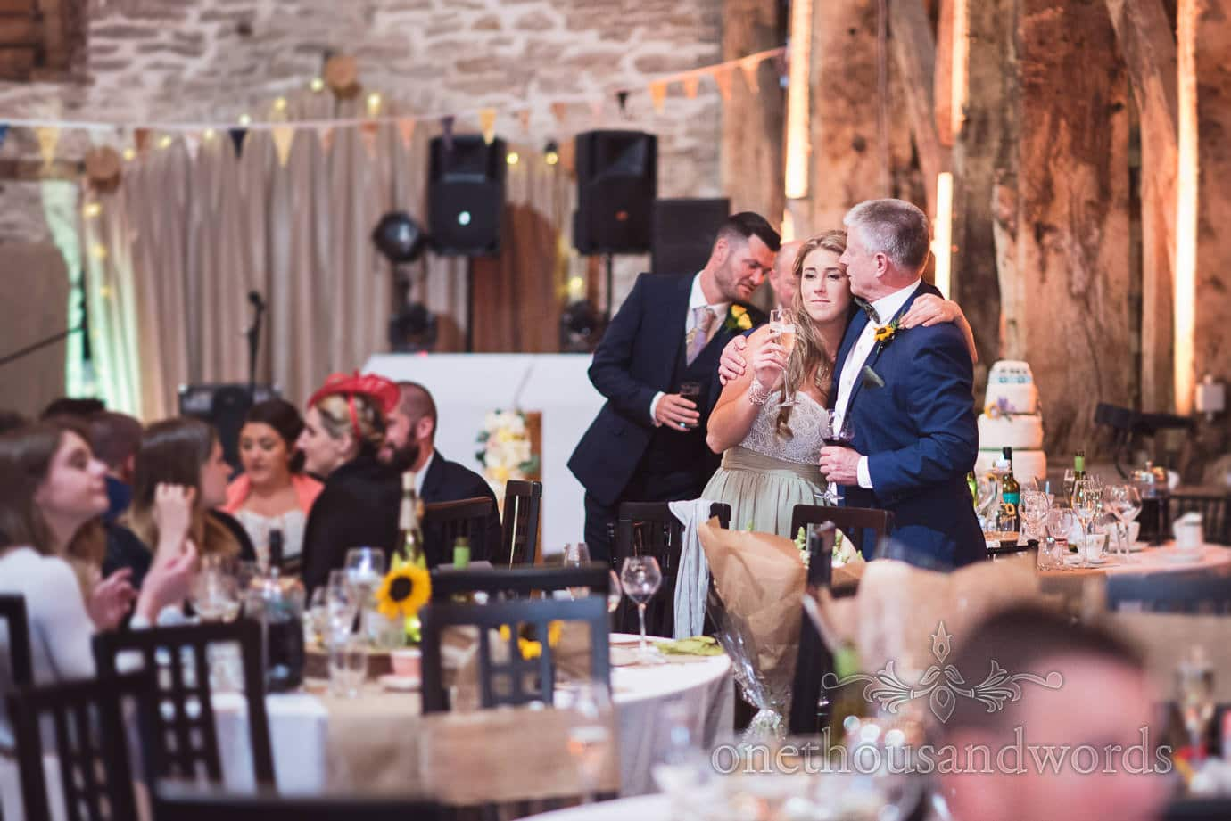 Father of the bride and bridesmaid embrace during wedding reception at rustic barn