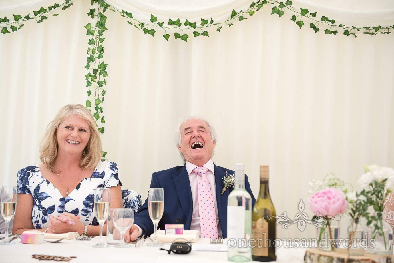 Father of the bride and mother of the groom laugh at wedding speeches on top table
