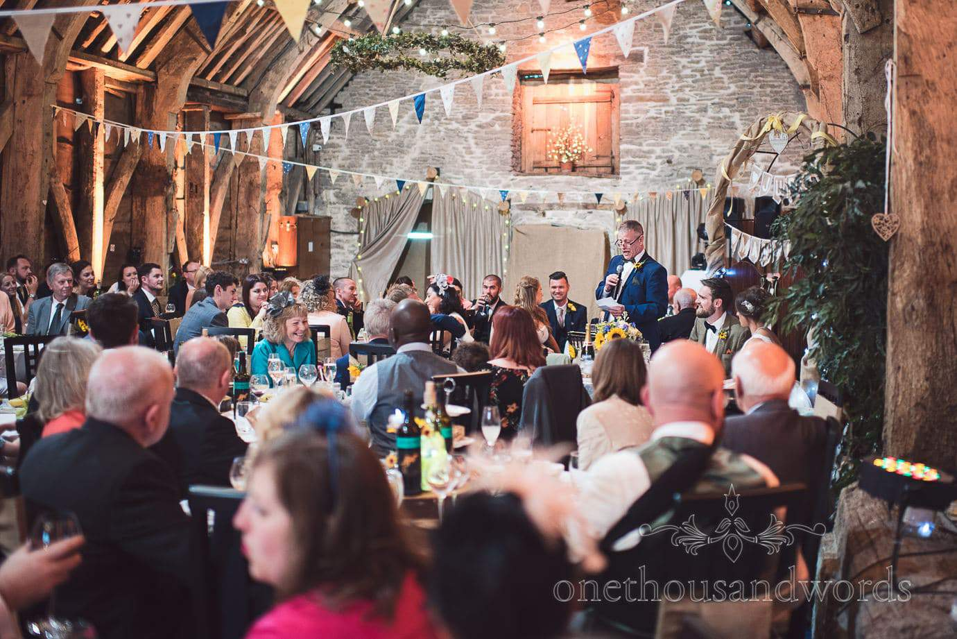 Father of the bride delivers speech at rustic barn wedding venue with bunting Stockbridge Farm barn