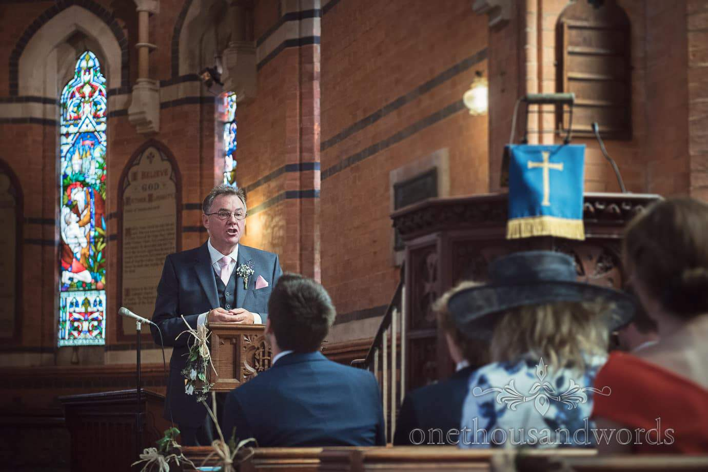 Father of the bride gives wedding reading in red brick church wedding ceremony