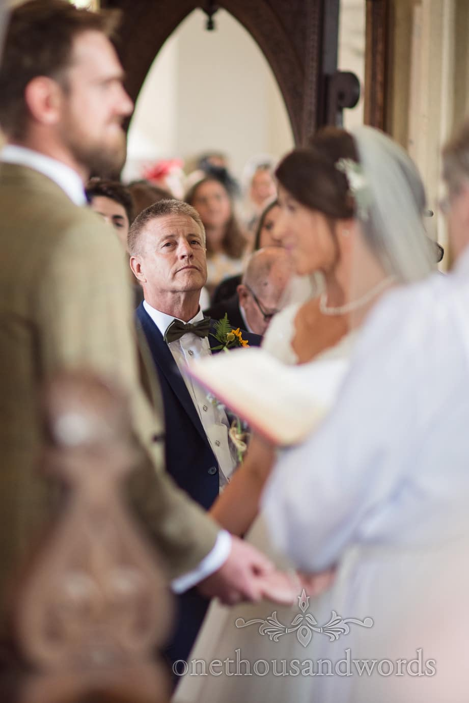 Father of the bride in bow tie watches his daughter's wedding ceremony in Church
