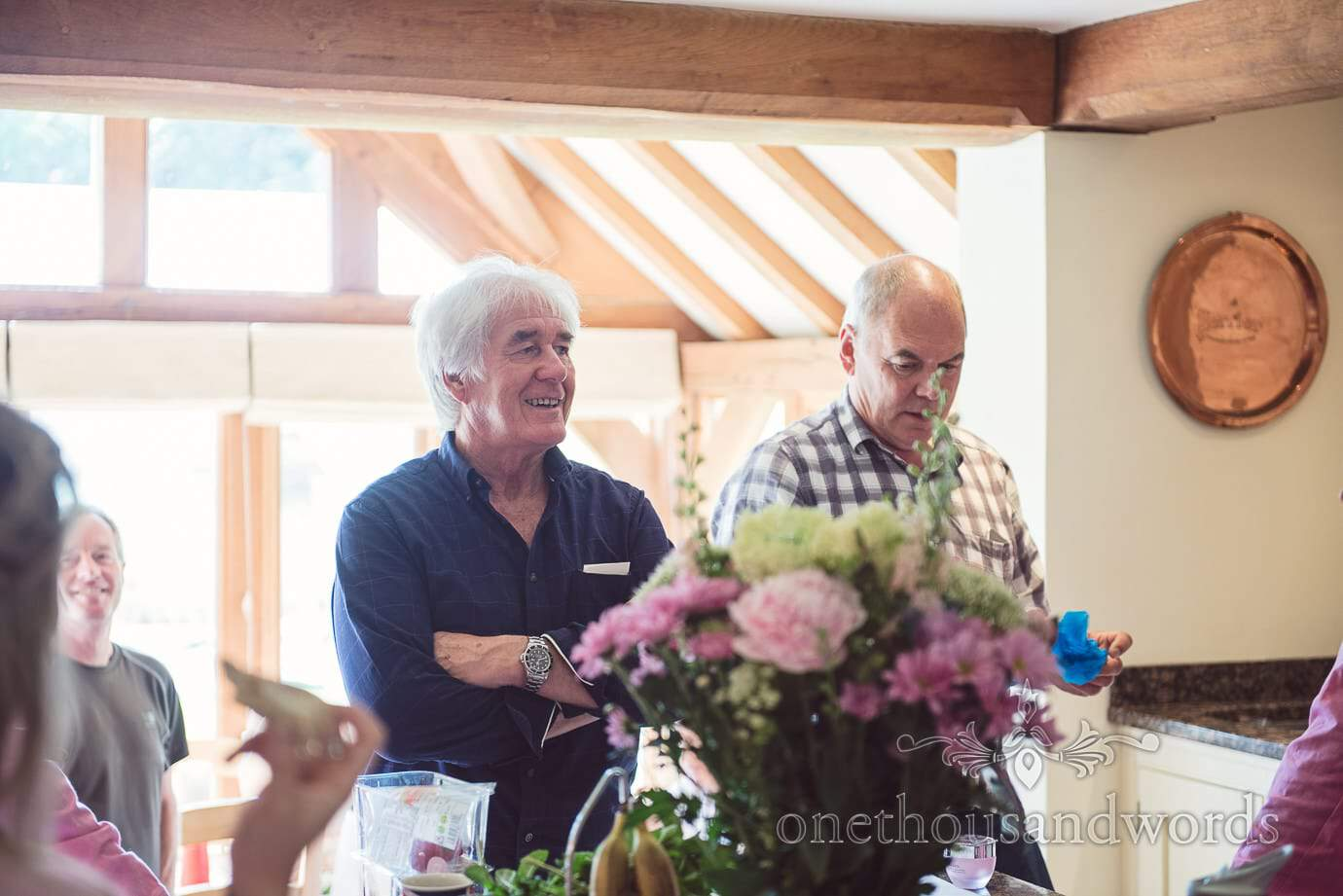 Father of the bride on wedding morning in kitchen with pink and cream flowers