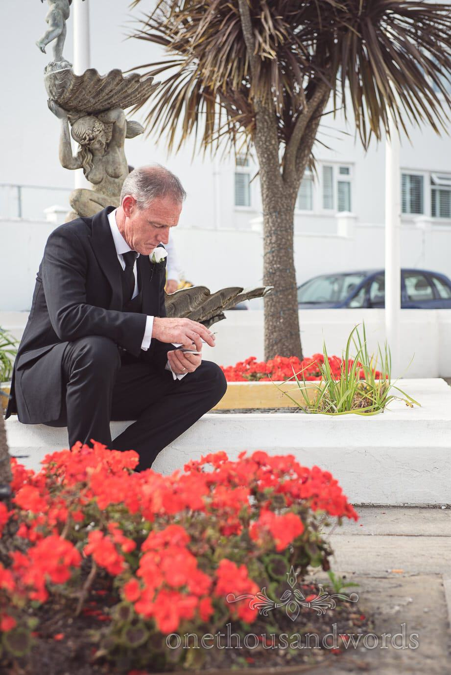 Father of the bride takes some time out to practice his wedding speech under a palm tree