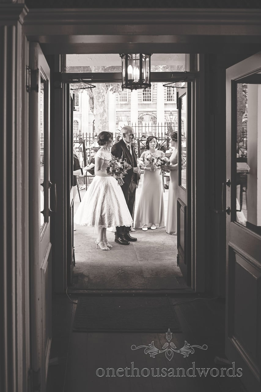 Father of the bride waits with bride and bridesmaids outside Trafalgar Tavern Wedding venue