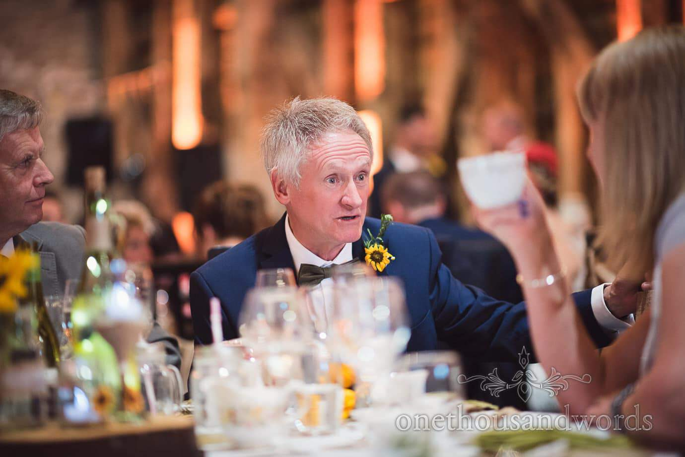Father of the groom in bow tie, sunflower button hole and blue suit during wedding breakfast