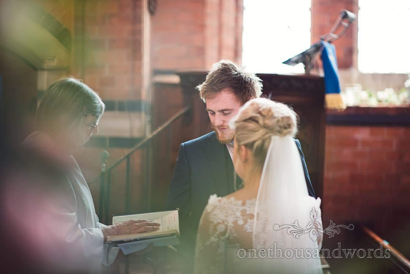 Female vicar reading during wedding ceremony in Tur Langton