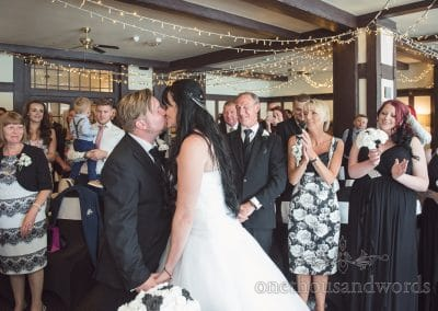 First kiss at back and white themed rock and roll wedding ceremony at Haven Hotel