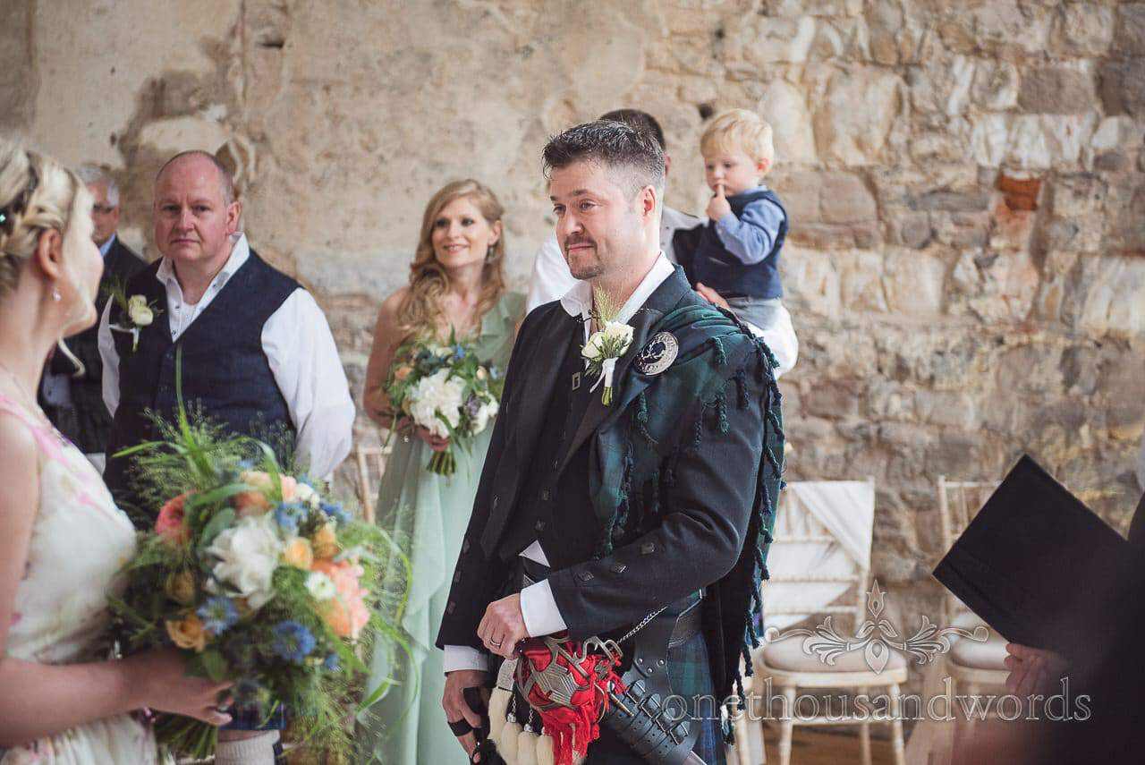 First look photograph of teary groom in traditional Scottish wedding outfit at Lulworth Castle