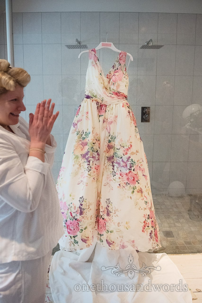 Floral designer wedding dress hangs in bathroom on wedding morning