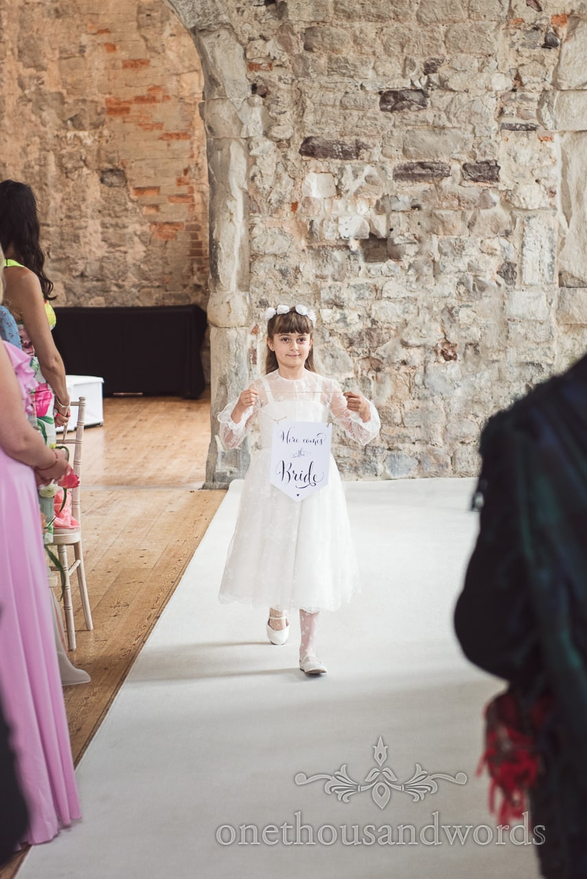 Flower girl carries Here Comes The Bride sign at Lulworth Castle wedding ceremony