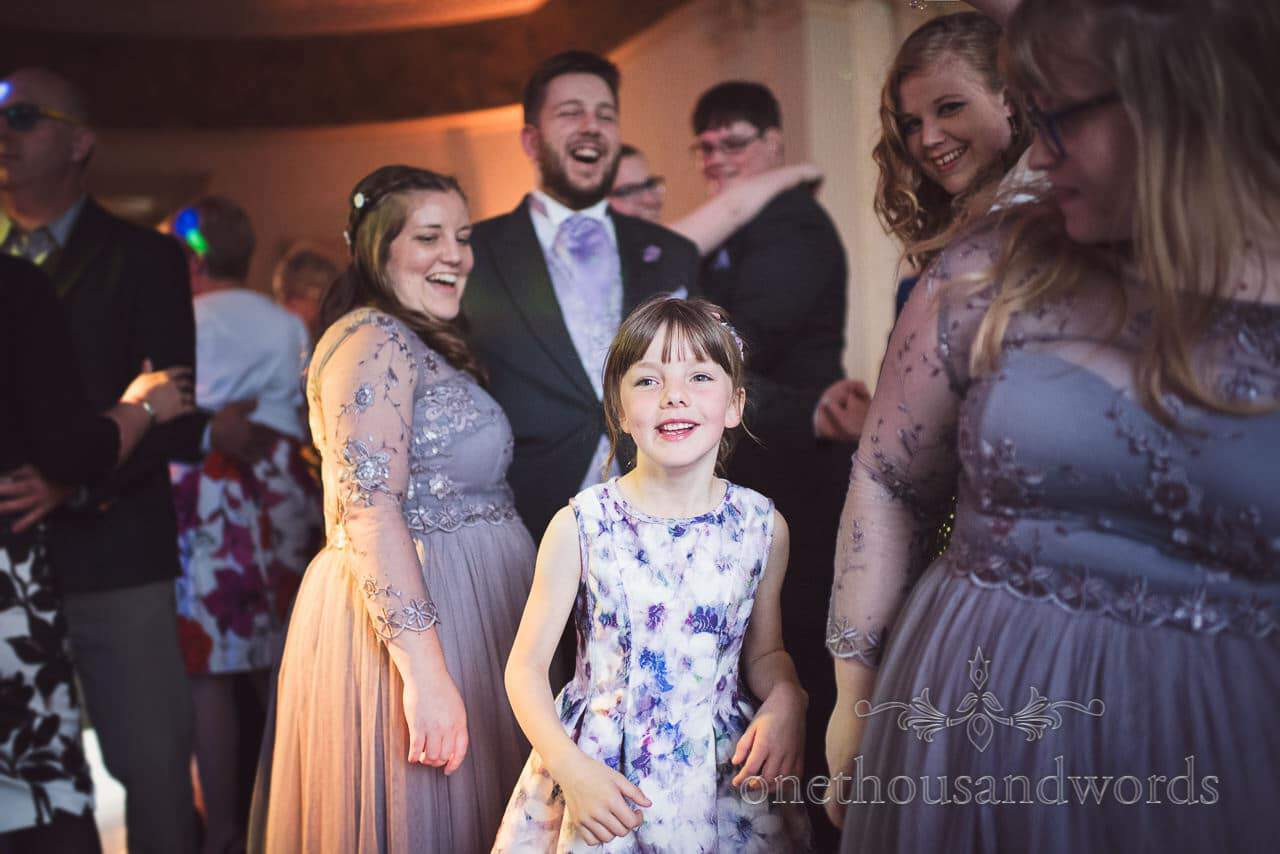 Flower girl dances with bridesmaids at Upton House wedding evening