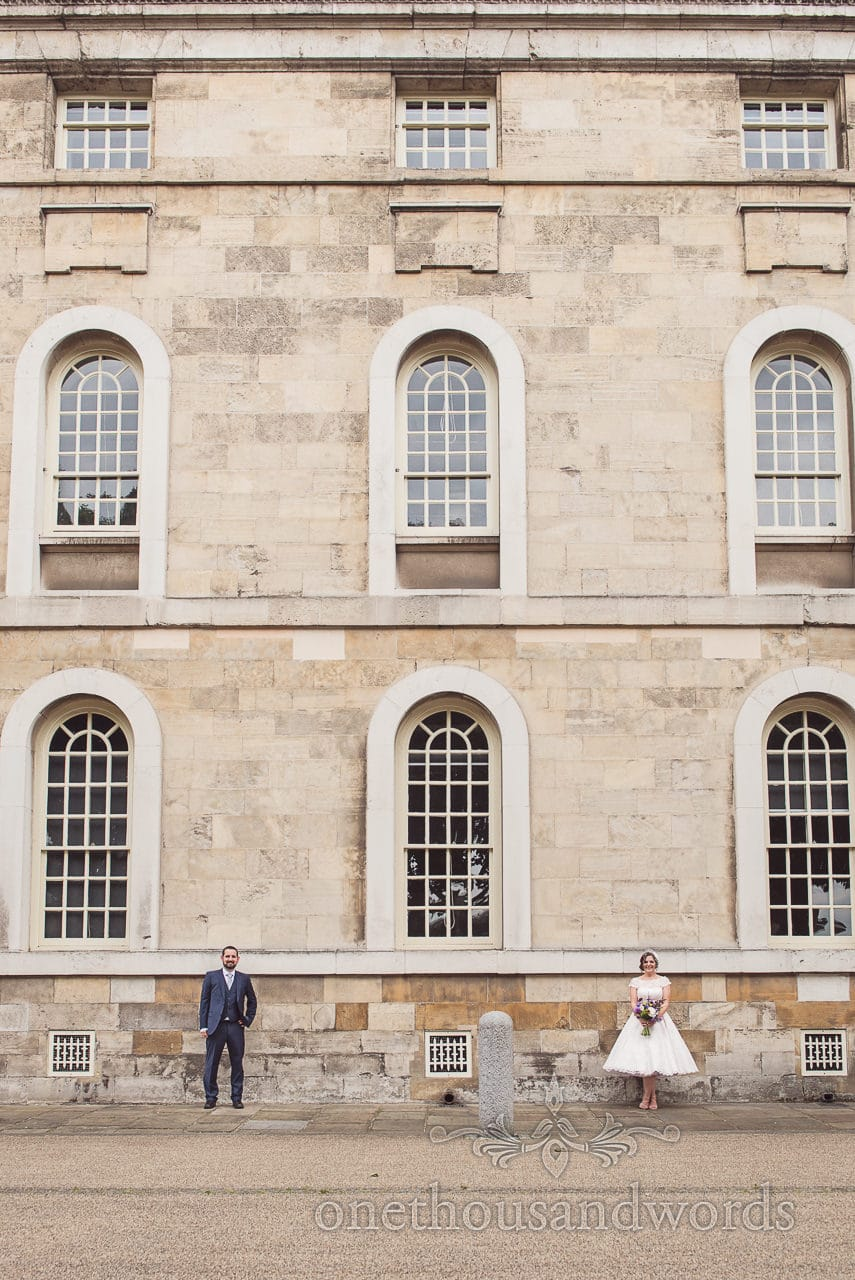 Greenwich wedding photographs of bride and groom next to huge stone building