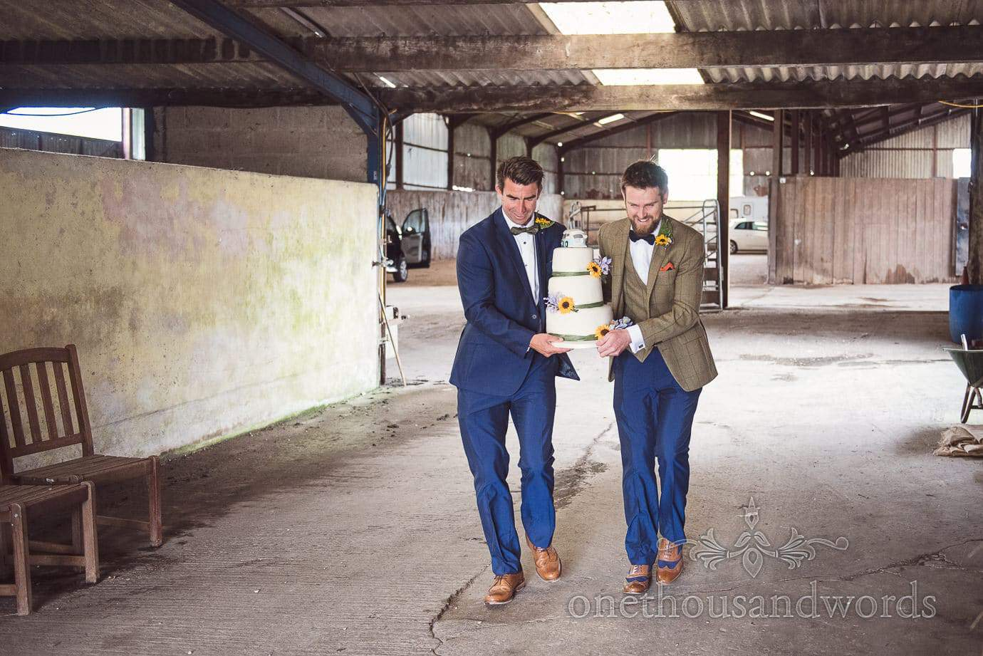Groom and grooms man with sunflowers carry wedding cake through farm barns