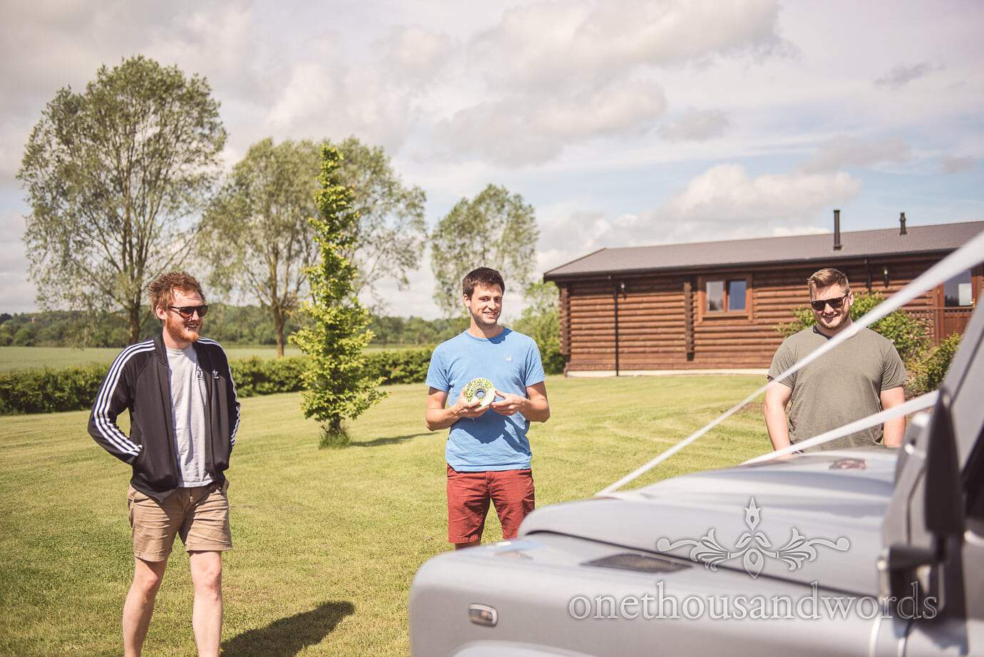 Groom and groomsmen add ribbon to wedding land rover on country wedding morning