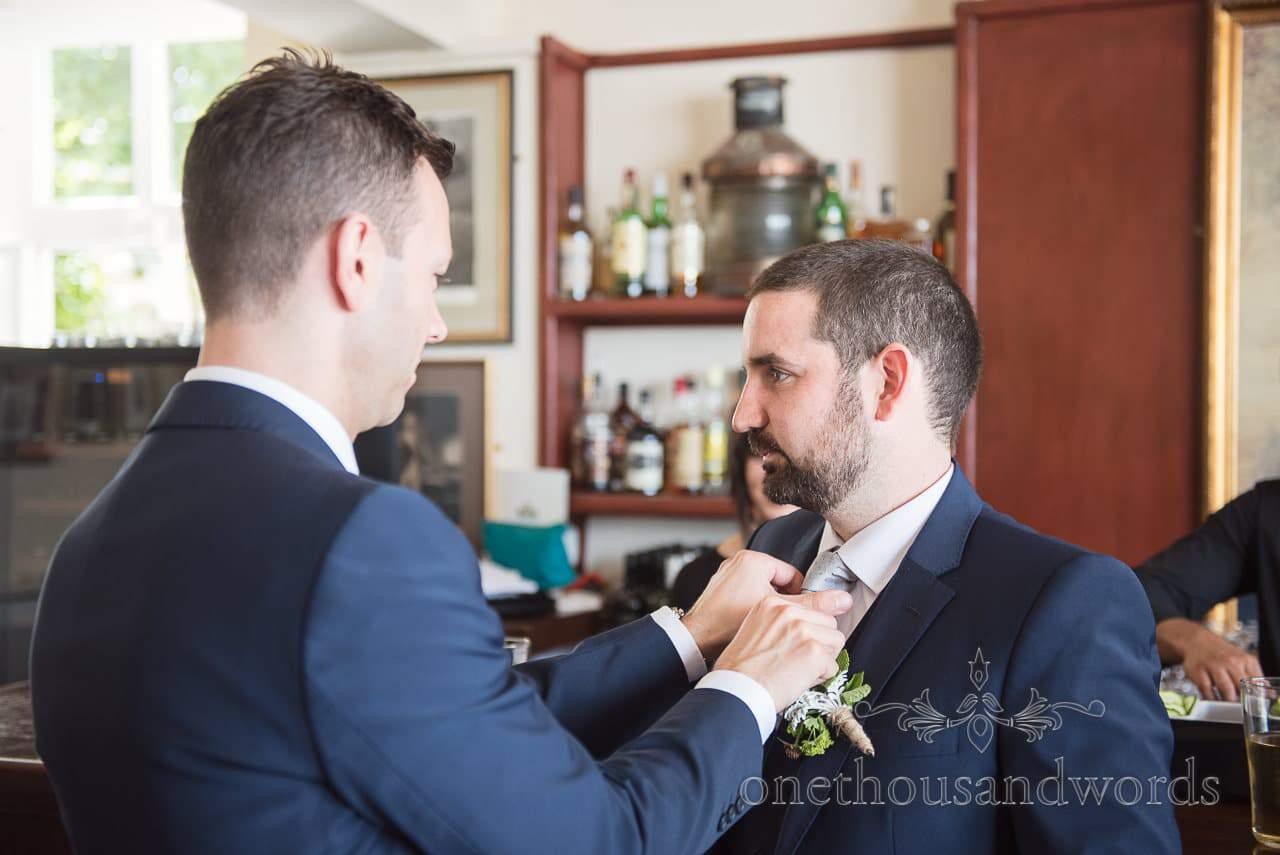 Groom had tie tied by grooms man in blue wedding suits at Trafalgar Tavern wedding